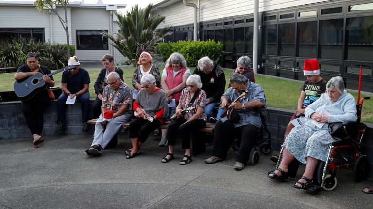 People observe a minute of silence as the pay their respects to the victims of the White Island volcano eruption, at the hospital in Whakatane, New Zealand