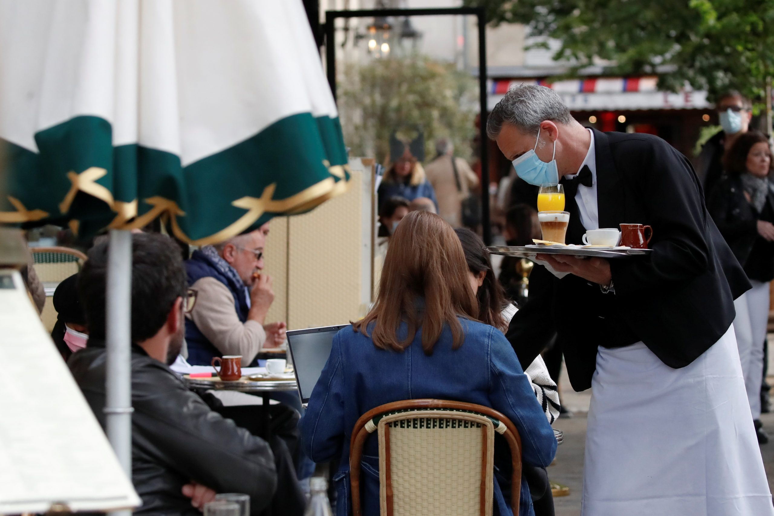 A waiter serves customers as cafes, bars and restaurants reopen their terraces after closing down for months, amid the coronavirus disease (COVID-19) outbreak, in Paris, France, May 19, 2021. REUTERS/Christian Hartmann